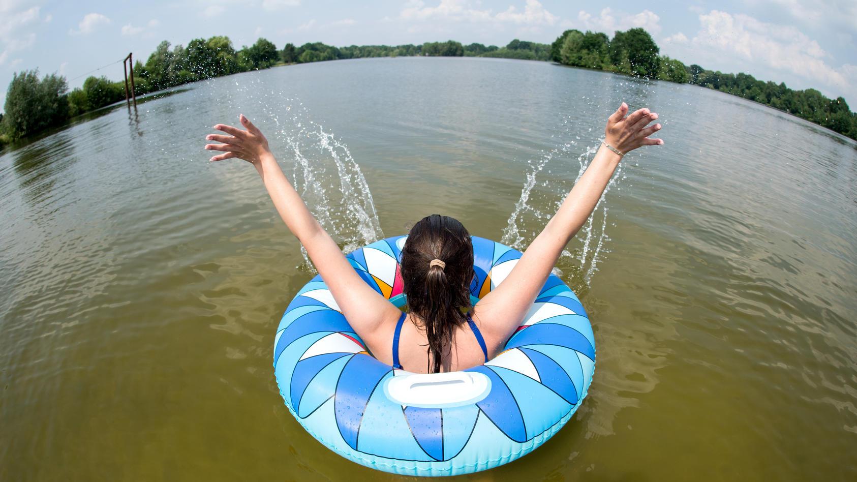 Ein junge Frau badet mit einem Schwimmreifen.