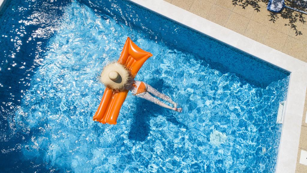Back view of woman relaxing on orange airbed in swimming pool model released Symbolfoto property released PUBLICATIONxINxGERxSUIxAUTxHUNxONLY MAEF12347