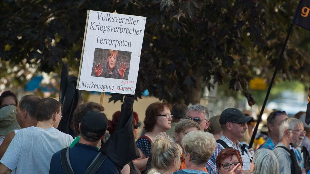ARCHIV - 16.08.2018, Sachsen, Dresden: Teilnehmer einer Demonstration der islamfeindlichen Pegida-Bewegung stehen anlässlich des bevorstehenden Besuchs von Bundeskanzlerin Merkel (CDU) im Sächsischen Landtag an einer Straßenkreuzung. Ein Mann hatte s