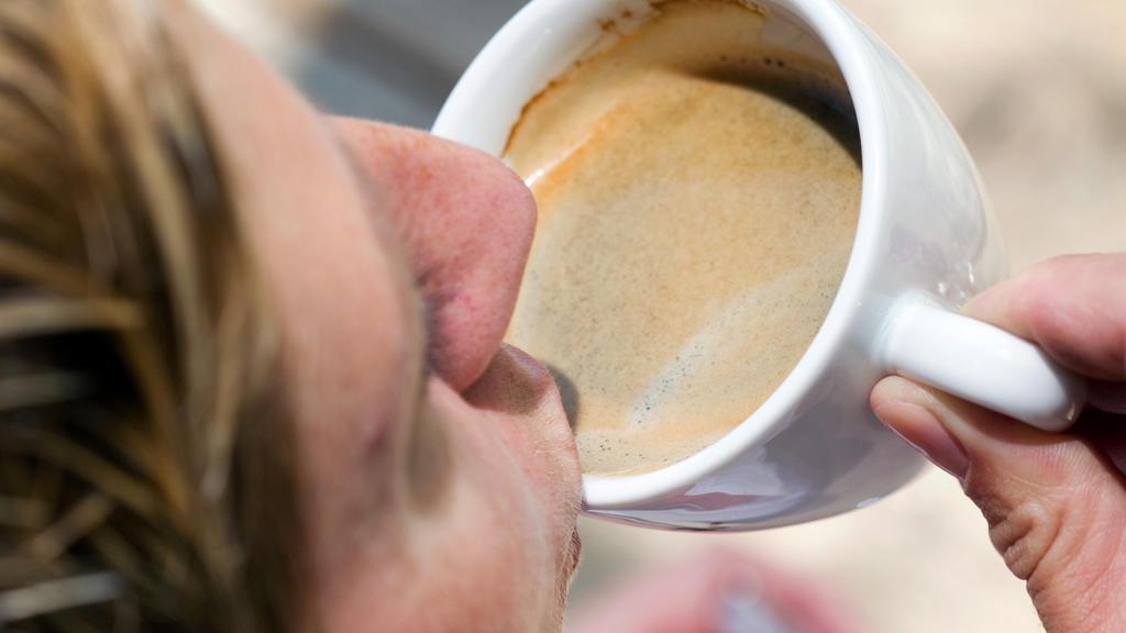 Eine Frau trinkt eine Tasse Kaffee-Crema. dpa