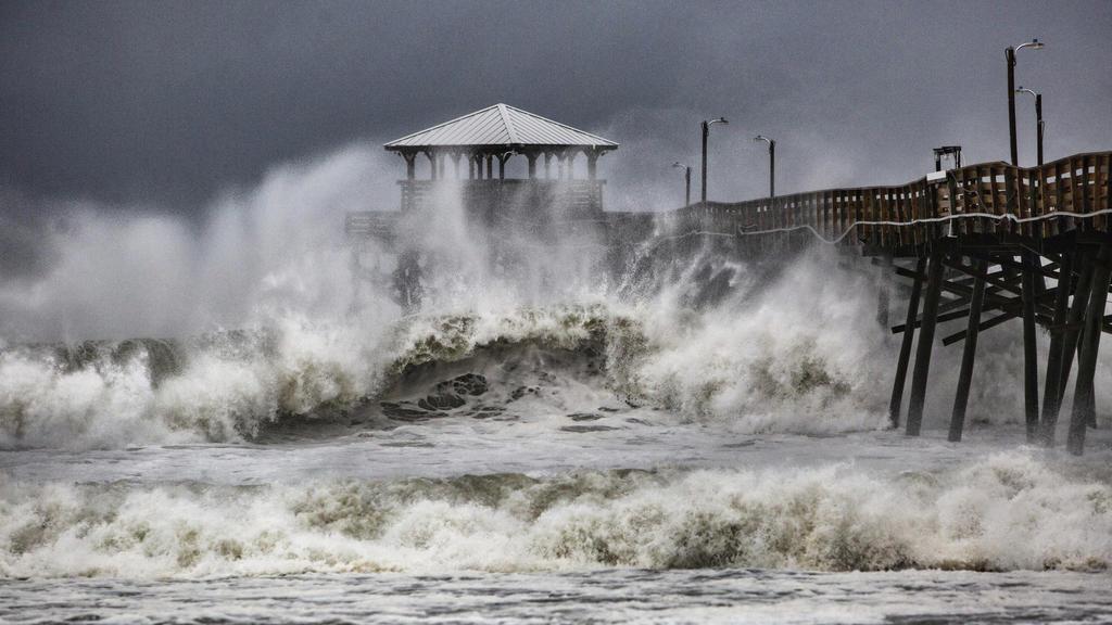 13.09.2018, USA, Atlantic Beach: Wellen brechen an einem Pier in Atlantic Beach während sich Hurrikan «Florence» der Region nähert. Der Hurrikan «Florence» soll nach Angaben der US-Behörden zwischen Freitag- und Samstagmorgen Ortszeit vermutlich in d