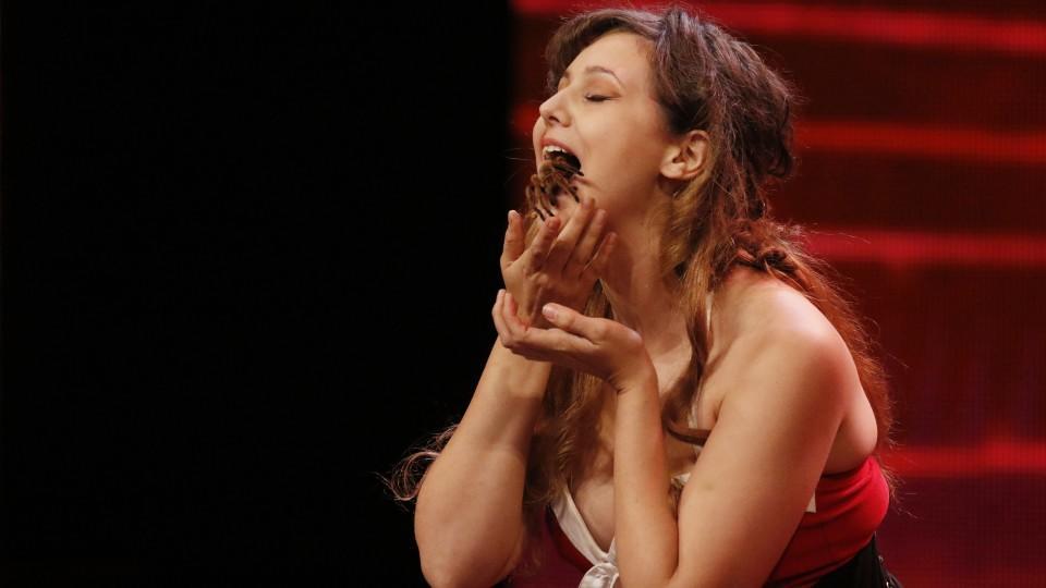 Marry Bleeds aus Amerika spielt mit einer Vogelspinne im Mund Mundharmonika.