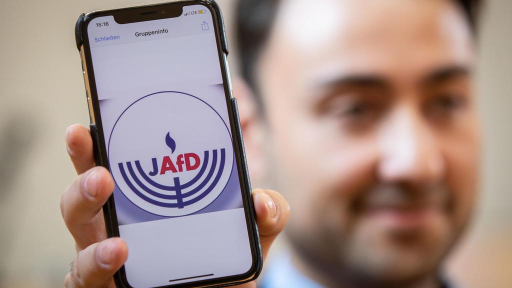 07.10.2018, Hessen, Wiesbaden: Beisitzer Leon Hakobian zeigt im Bürgerhaus im Stadtteil Erbenheim auf seinem Handy den vorläufigen Entwurf eines Logos der jüdischen Bundesvereinigung innerhalb der AfD, die wenig später gegründet werden sollte. Foto: