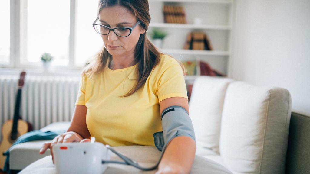 Eine Frau mittleren Alters misst ihren Blutdruck