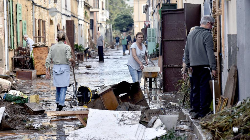 Several residents collaborate in the cleaning works of the streets in the village of Sant Llorenc des Cardasar, in Mallorca island, eastern Spain, 10 October 2018, a day after the flash floods hitting the area. At least ten people died and 5 years-ol