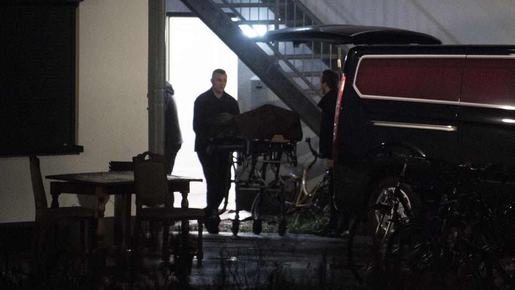 Bestatter transportieren aus einer städtischen Unterkunft eine Leiche ab.