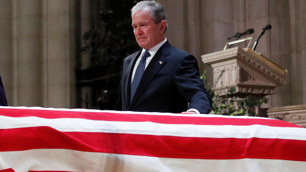 Former President George W. Bush touches the casket of his father, former President George H.W. Bush, at the State Funeral at the National Cathedral, Wednesday, Dec. 5, 2018, in Washington. Alex Brandon/Pool via REUTERS