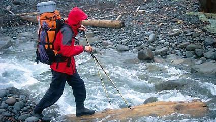 Ein Wanderer mit Regenkleidung, Rucksack und Wanderstock geht gerade auf einem Baumstamm über einen Bergbach.