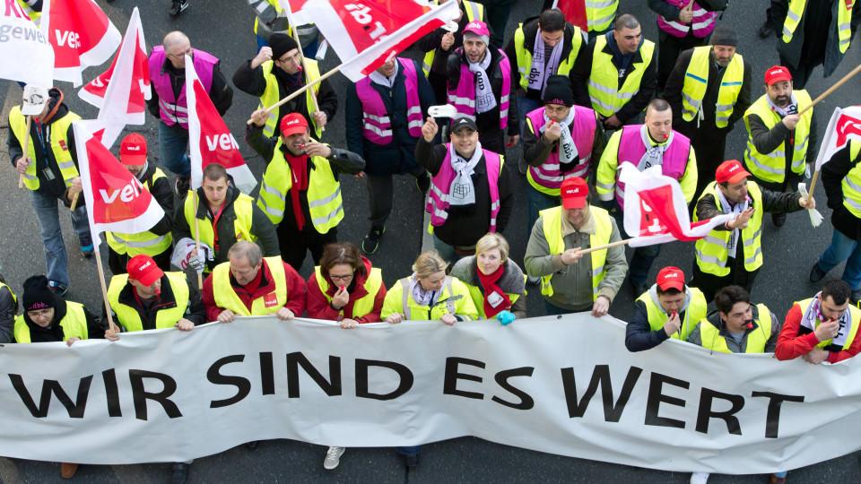 """ARCHIV - Mitglieder verschiedener Gewerkschaften protestieren am 27.03.2014 vor dem Flughafen in Frankfurt am Main (Hessen) und halten dabei ein Banner mit der Aufschrift «Wir sind es Wert».  Foto: Boris Roessler/dpa  (zu dpa """"Ganz Hessen von Verdi-W"""