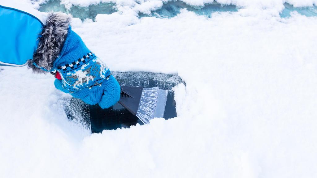 Mensch befreit Autoscheibe von Schnee und Eis.