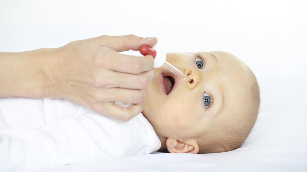 Baby hat Schnupfen und bekommt Nasentropfen.