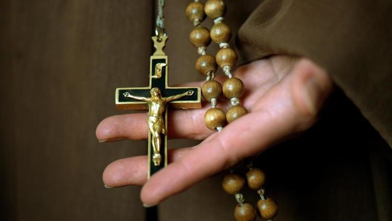 Ein Novize hält sein Kruzifix am Rosenkranz in den Händen. Foto: Arno Burgi/Archiv