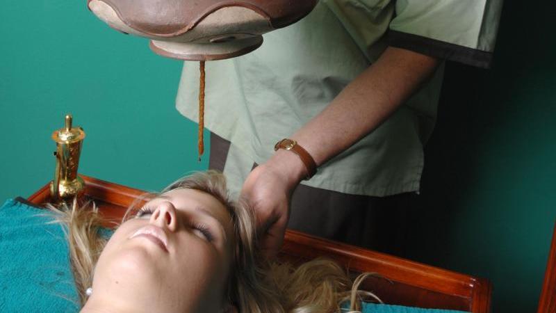 Eine Frau erhält eine traditionelle Ayurveda-Anwendung.