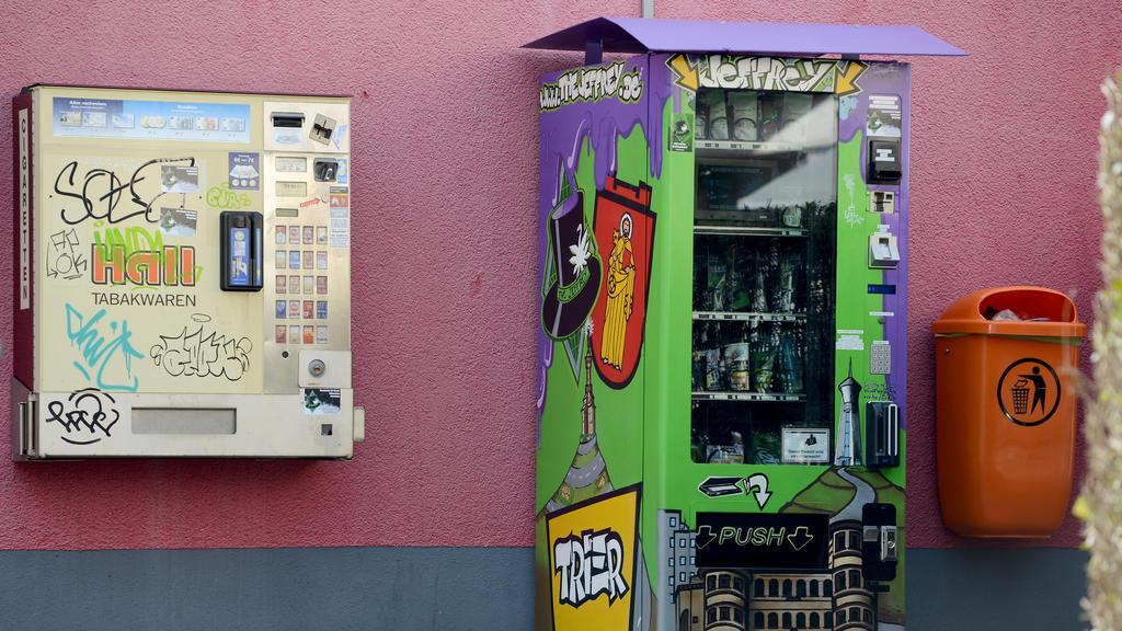 21.03.2019, Rheinland-Pfalz, Trier: Ein Cannabis-Automat (r), der gepresste und getrocknete Cannabis-Blüten in Tütchen sowie Extrakt-Kügelchen in Plastikdöschen plus allerlei Rauchzubehör zum Kauf enthält, steht auf der Straße neben einem Tabakautoma