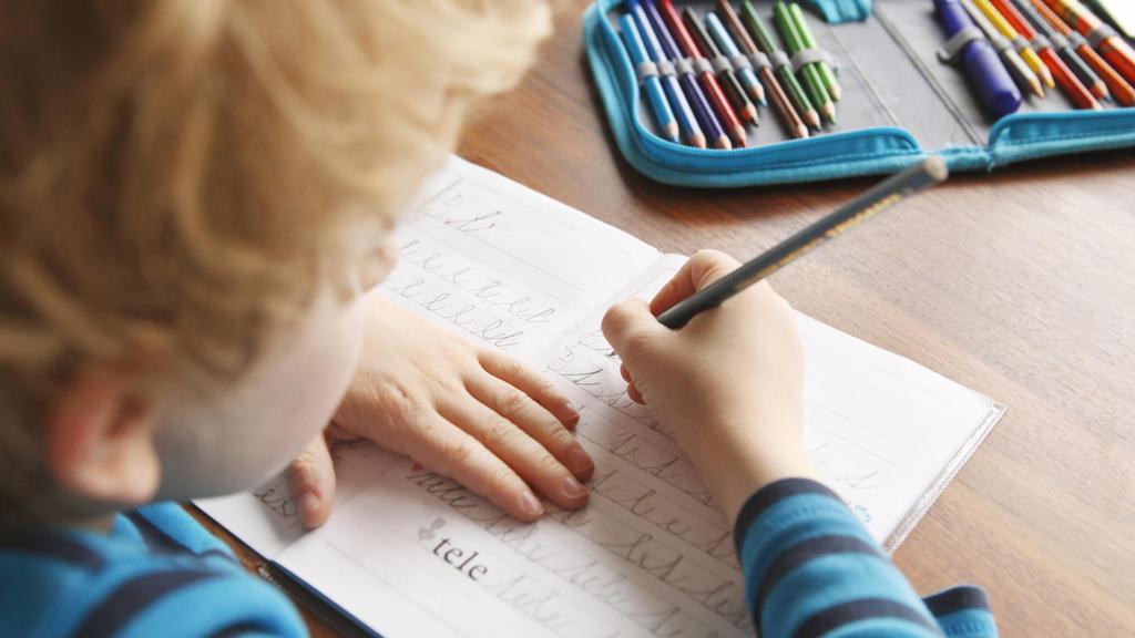 Kind lernt schreiben und lesen.
