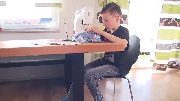 Nico sitzt an der Nähmaschine