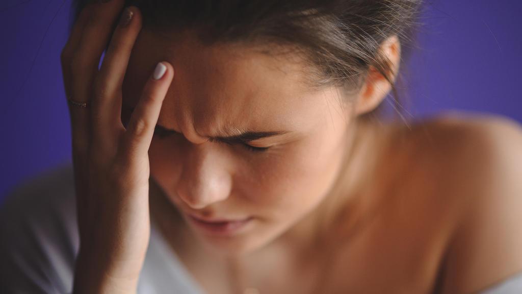 Junge Frau mit Migräne