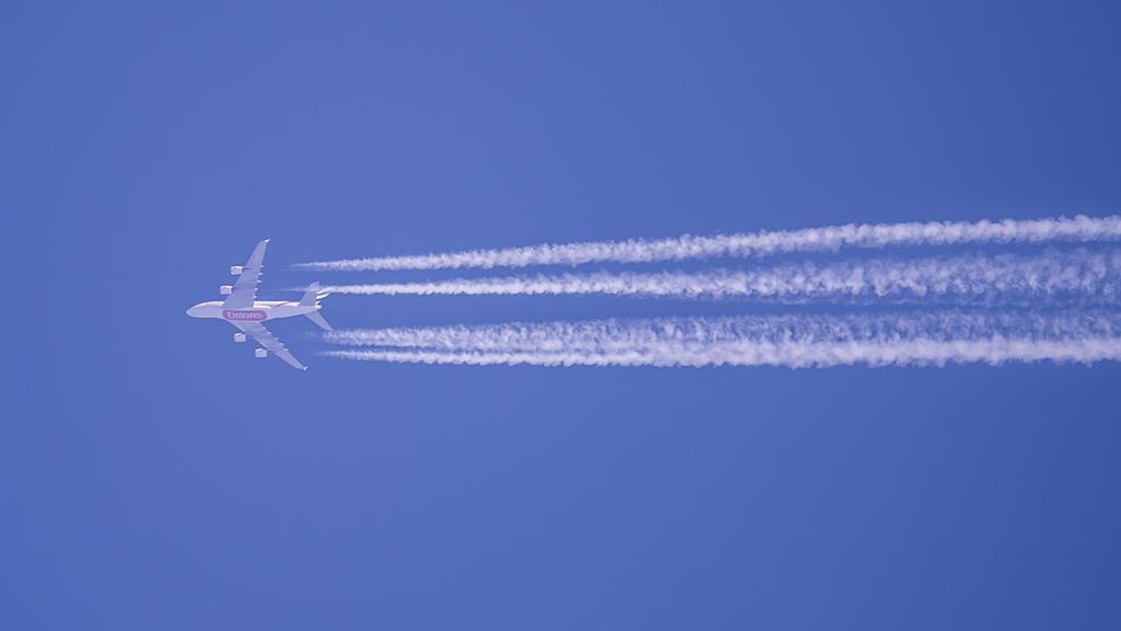 Kondensstreifen eines Flugzeugs der Fluggesellschaft Qatar Airways sind am blauen Himmel zu sehen.