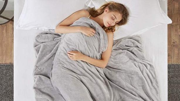 Schlafende Frau mit Gewichtsdecke