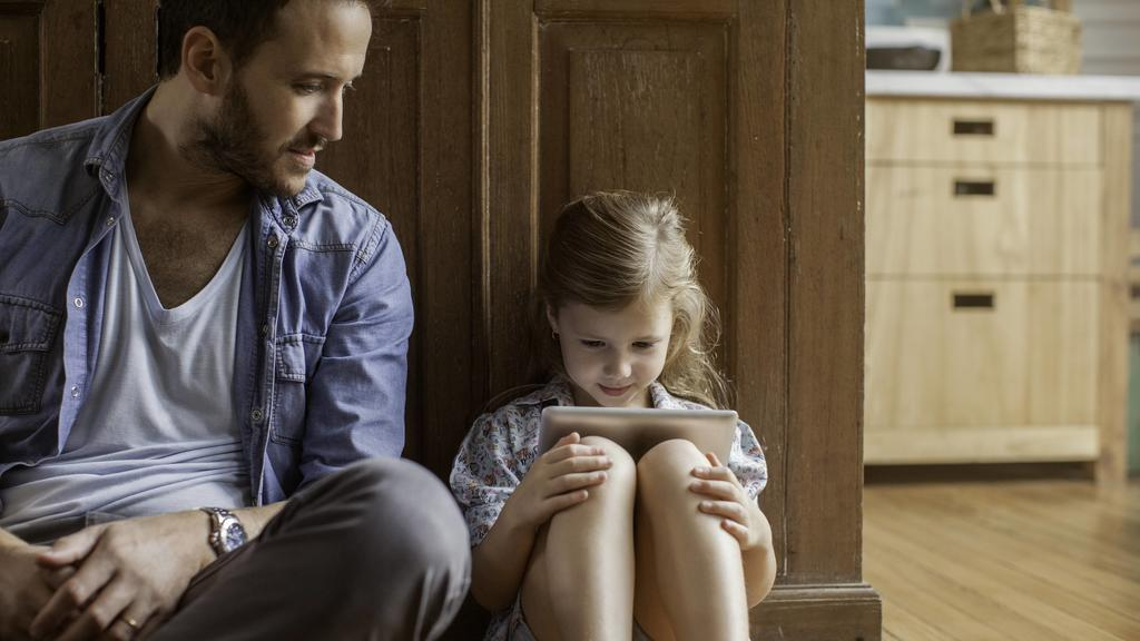 Father watching as daughter plays video game PUBLICATIONxINxGERxSUIxAUTxONLY Copyright: SigridxOlsson B61496922
