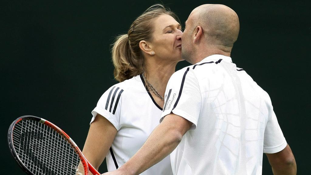 Großbritannien, London: Die ehemalige deutsche Tennisspielerin Steffi Graf und ihr Mann Andre Agassi küssen sich nach einem Showturnier in Wimbledon.  (zu dpa: ««Man hat sie nicht umsonst die Gräfin genannt» - Steffi Graf wird 50