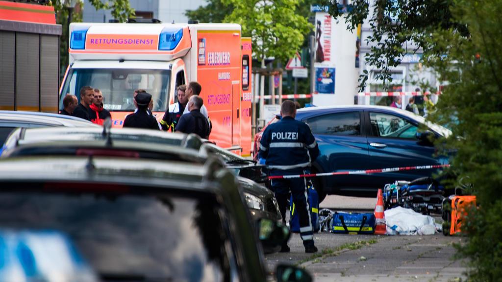 27.06.2019, Hamburg: Polizisten und Feuerwehrleute, stehen an einer abgesperrten Straße neben einem abgedeckten Körper. Ein Mann ist in Hamburg-Lohbrügge am erschossen worden. Einzelheiten oder Hintergründe konnte ein Sprecher des Lagezentrums der Po