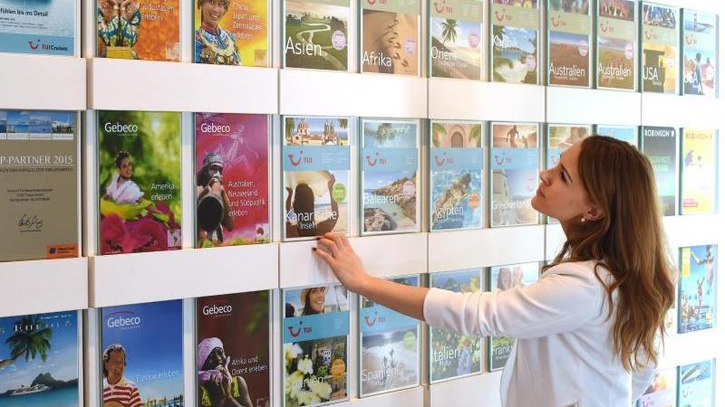 Eine Frau blickt in einem Reisebüro auf Kataloge. Foto: Jens Kalaene/Archiv