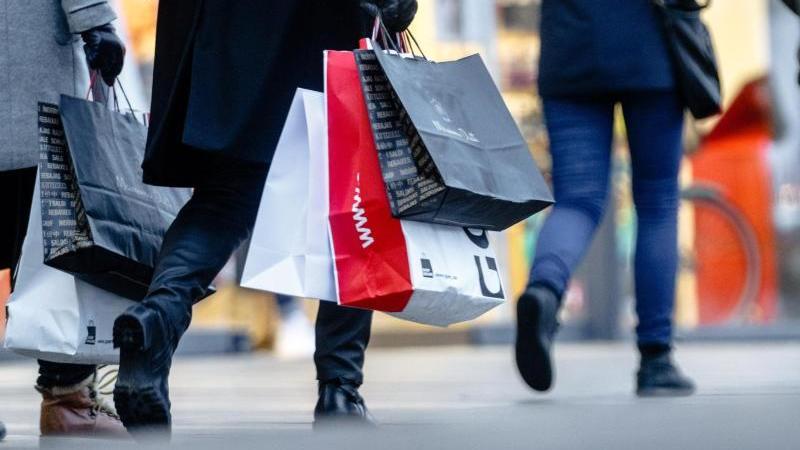 Passanten mit Einkaufstüten an einem verkaufsoffenen Sonntag. Foto: Markus Scholz/Archivbild
