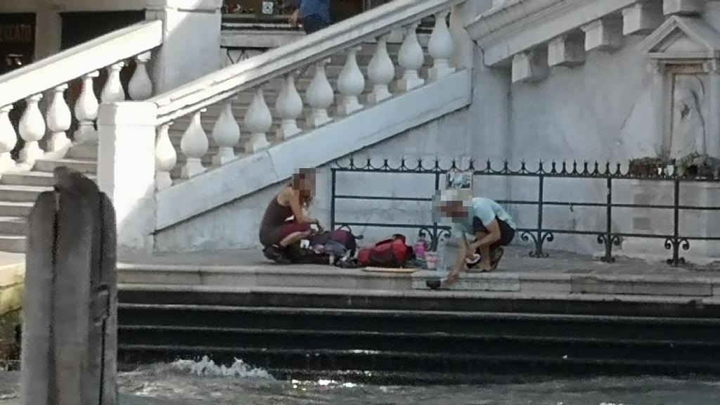 """HANDOUT - 19.07.2019, Italien, Venedig: Zwei deutsche Touristen sitzen mit ihrem Gepäck an der Treppe der Rialto-Brücke und kochen sich mit einem kleinen Kaffeekocher einen Kaffee auf dem Gehweg. (zu dpa """"Deutsche Touristen kochen Kaffee in Venedig -"""