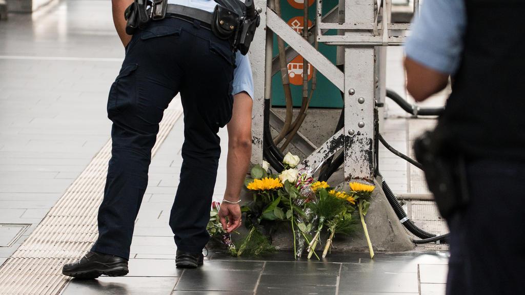29.07.2019, Hessen, Frankfurt/Main: Ein Polizist legt an einer Stelle im Hauptbahnhof Blumen nieder. Ein achtjähriger Junge ist im Frankfurter Hauptbahnhof von einem Mann vor einen einfahrenden ICE gestoßen und getötet worden. Ein Tatverdächtiger wur