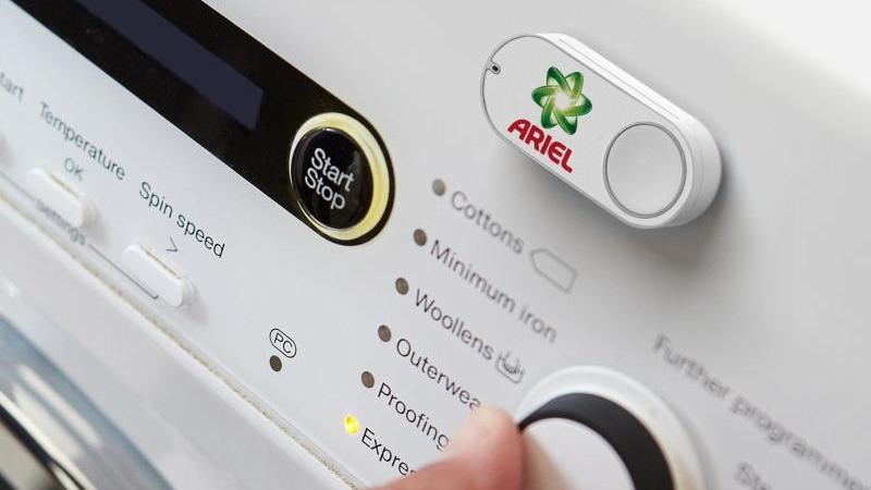 Ein Amazon Dash Button für die Marke Ariel klebt an einer Waschmaschine. Foto: Amazon