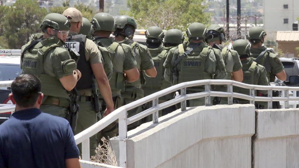 03.08.2019, USA, El Paso: Mitglieder einer Spezialeinheit der Polizei warten in der Nähe eines Ladenkomplexes, in dem ein Mann zahlreiche Menschen erschossen hat. Die Hintergründe der Tat blieben zunächst unklar. Foto: Mark Lambie/The El Paso Times/A