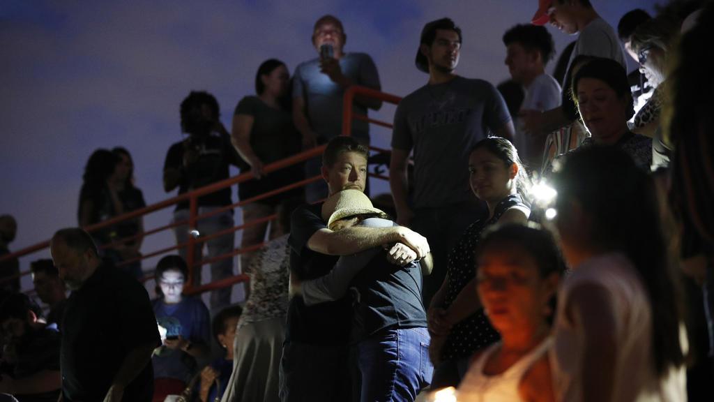 03.08.2019, USA, El Paso: Menschen umarmen sich während einer Mahnwache nachdem ein Schütze in einem Einkaufszentrum mindestens 20 Menschen getötet und mindestens 26 weitere verletzt hatte. Es gibt Hinweise, dass es sich um ein Hassverbrechen handeln