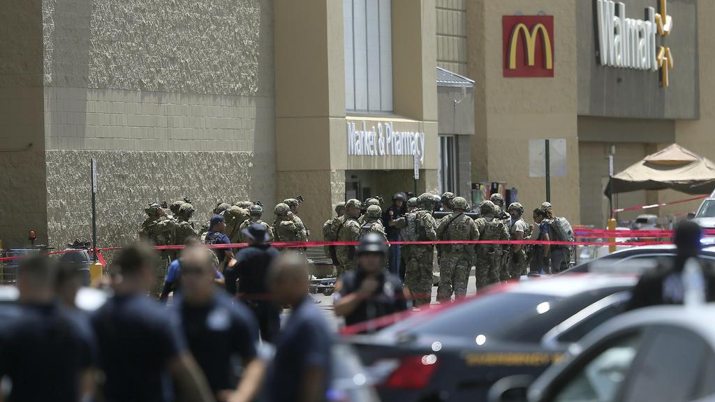 03.08.2019, USA, El Paso: Mitglieder einer Spezialeinheit und Polizisten stehen vor dem Eingang eines Ladenkomplexes, in dem ein Mann zahlreiche Menschen erschossen hat. Die Hintergründe der Tat blieben zunächst unklar. Foto: Mark Lambie/The El Paso