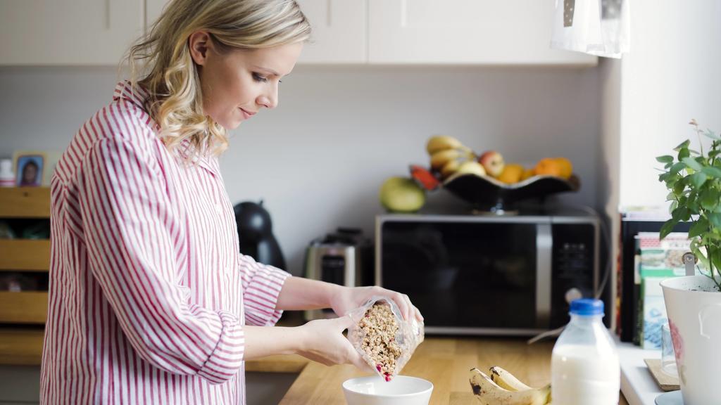 Eine Frau bereitet sich in der Küche ein gesundes Frühstück, bestehend aus Müsli und Joghurt, zu.