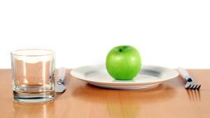 Gedeckter Tisch mit einem Apfel auf dem Teller.