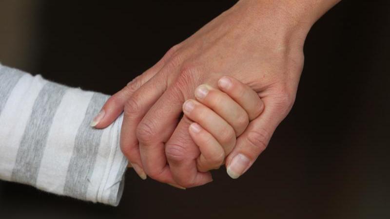 Eine Frau hält die Hand eines Kindes 8Symbolbild). Foto: Karl-Josef Hildenbrand/Archivbild