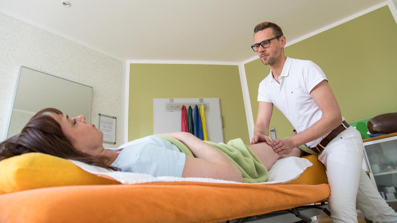 Ein Physiotherapeut behandelt eine Patientin mit Lymphdrainage.