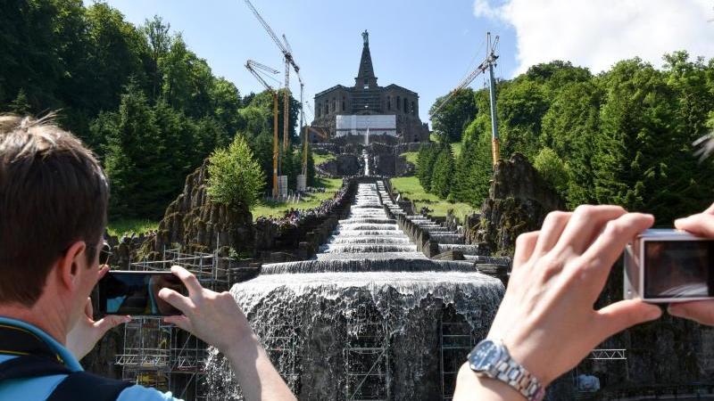 Touristen fotografieren Wasserspiele im Kasseler Bergpark