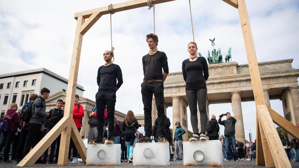 dpatopbilder - 20.09.2019, Berlin: Drei Demonstranten stehen unter einem Galgen mit einem Seil um den Hals auf Eisblöcken. Dahinter ist das Brandenburger Tor. Die Bewegung Fridays for Future hatte zum globalen Klimastreik aufgerufen. Foto: Tom Weller