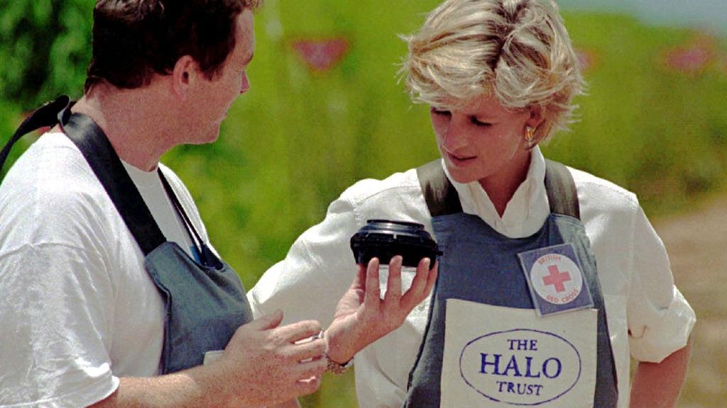 ARCHIV - 15.01.1997, Angola, Huambo: Ausgestattet mit einer Weste, die vor Splittern schützt, hört Diana, Prinzessin von Wales, den Erklärungen eines mit dem Räumen von Minenfeldern beauftragten Experten zu. Diana war nach Huambo gereist, um Experten