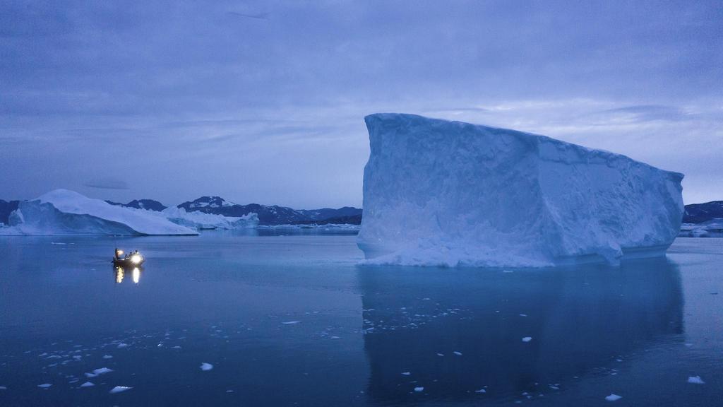 ARCHIV - 15.08.2019, Grönland, Kulusuk: Ein kleines Boot fährt an einem großen Eisberg in Ostgrönland vorbei. Mit der Erderwärmung dehnt sich das Meerwasser aus, die Eismassen schmelzen und der Meeresspiegel steigt. Den Einfluss von CO2 auf Meer und