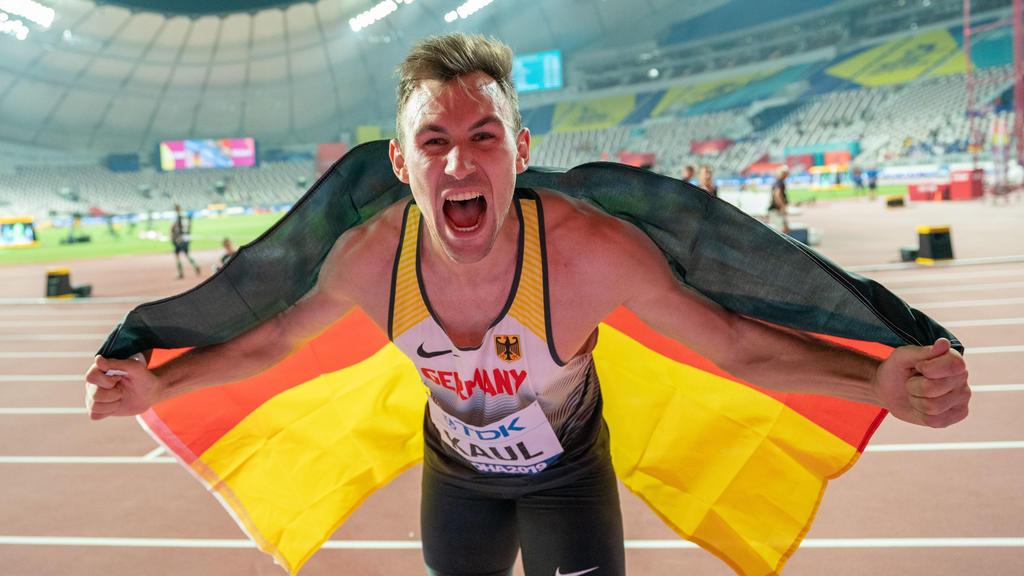 Zehnkämpfer Niklas Kaul posiert bei der Leichtathletik-WM in Katar mit Deutschland-Flagge