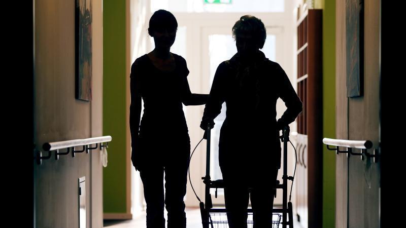 Eine Pflegerin (l) begleitet die Bewohnerin eines Altenheims beim Gang über den Flur. Foto: Oliver Berg/dpa