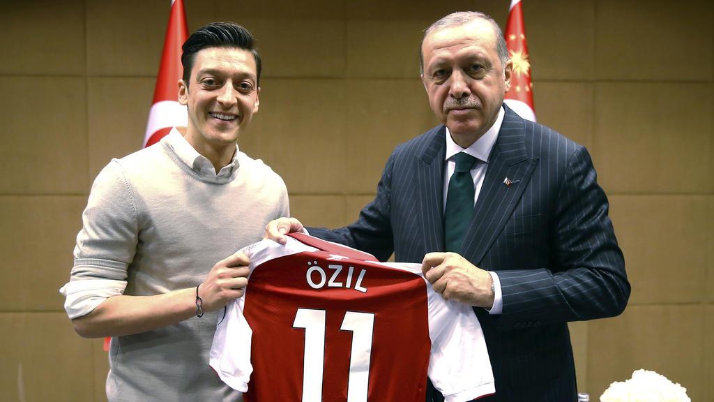 ARCHIV - 14.05.2018, Großbritannien, London: Recep Tayyip Erdogan, Staatspräsident der Türkei, hält zusammen mit Fußballspieler Mesut Özil vom englischen Premier League Verein FC Arsenal, ein Trikot von Özil. Ex-Nationalspieler Mesut Özil hat knapp 1