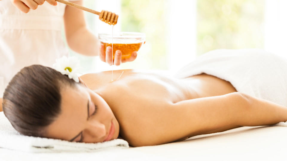 Masseuse pouring honey on woman's back