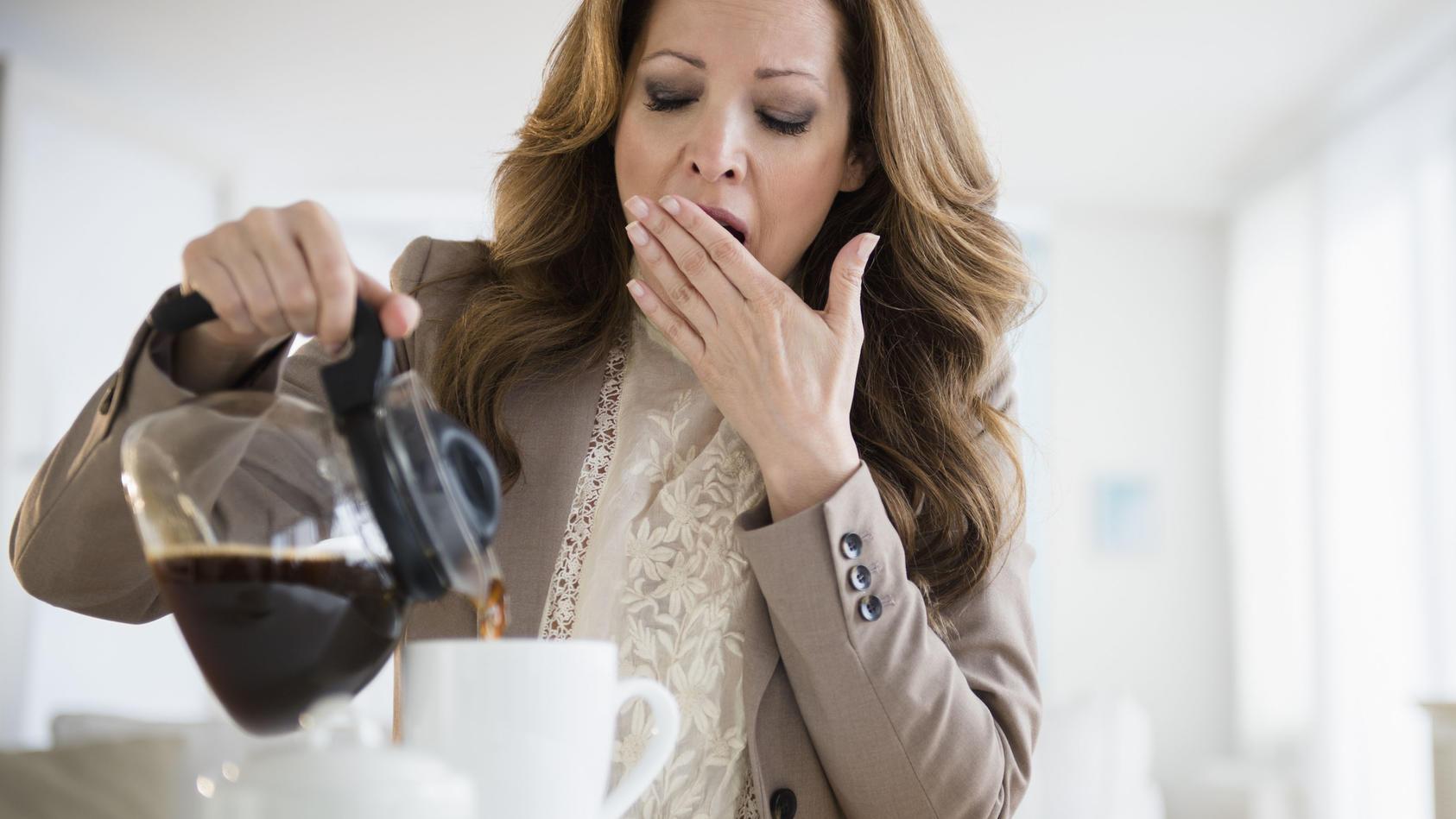 Gähnende Frau trinkt Kaffee.
