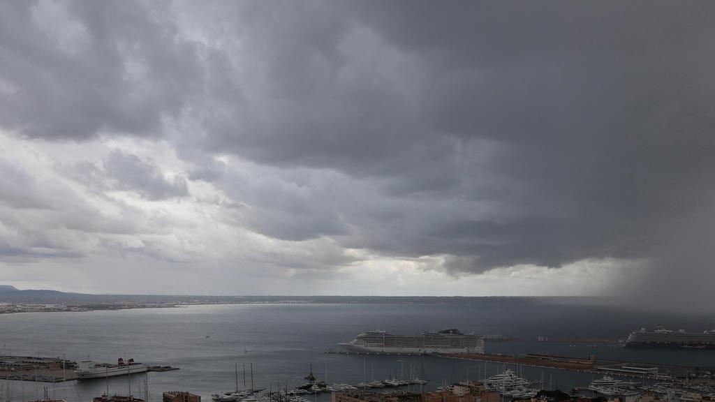 23.10.2019, Spanien, Palma de Mallorca: Dunkle Regenwolken hängen über der Bucht und dem Hafen, in dem zwei Kreuzfahrtschiffe liegen. Rund ums Mittelmeer haben heftige Unwetter vielerorts Überflutungen und Schäden  verursacht. Foto: Clara Margais/dpa