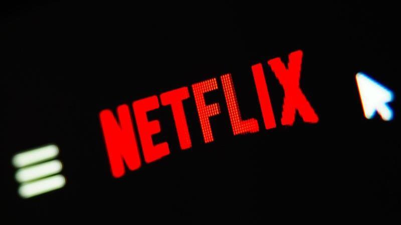 """Ein Mauszeiger ist auf einem Computerbildschirm neben dem Logo von """"Netflix"""" zu sehen. Foto: Nicolas Armer/dpa/Archivbild"""