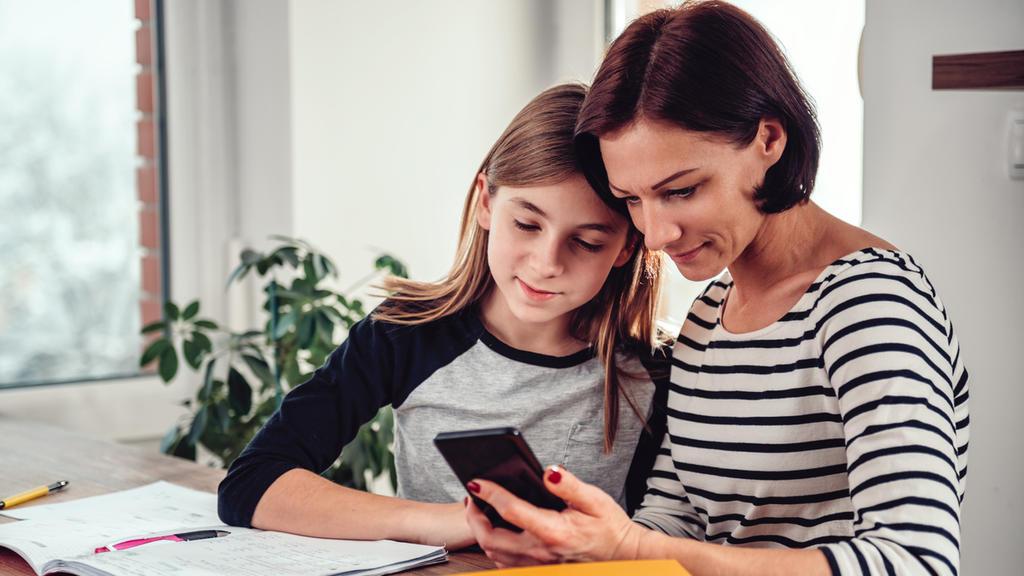 Mutter und Tochter schauen zusammen auf Smartphone
